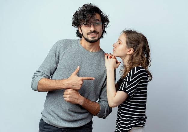 Jong koppel man en vrouw, vrouw schouder van haar vriendje aan te raken terwijl hij met de vinger naar haar wijst op een witte achtergrond