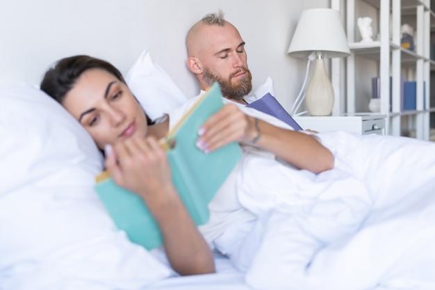 Jong koppel man met vrouw thuis in bed boeken lezen in de herfst winteravond, man viel in slaap