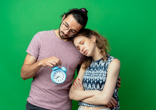 Jong koppel man met wekker en knuffelen zijn trieste vriendin staande over groene muur