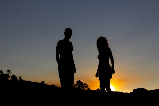 Jong koppel met achtergrondverlichting bij zonsondergang. ruimte kopiëren.