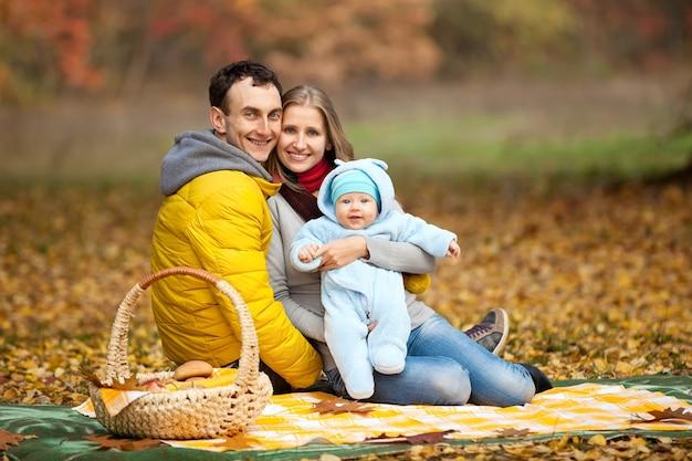 Jong koppel met babyjongen op picknick in herfst park