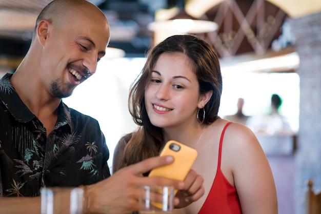 Jong koppel met behulp van een mobiele telefoon terwijl u samen geniet van een date in een restaurant.