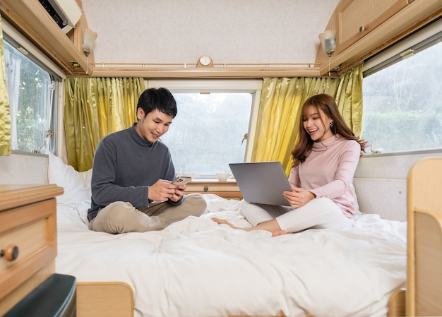 Jong koppel met behulp van smartphone en laptopcomputer op bed van een camper rv busje camper