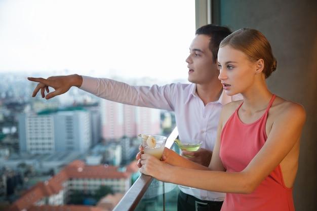 Jong koppel met cocktails staande op een balkon