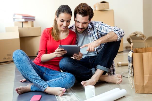 Jong koppel met digitale tablet in hun nieuwe huis