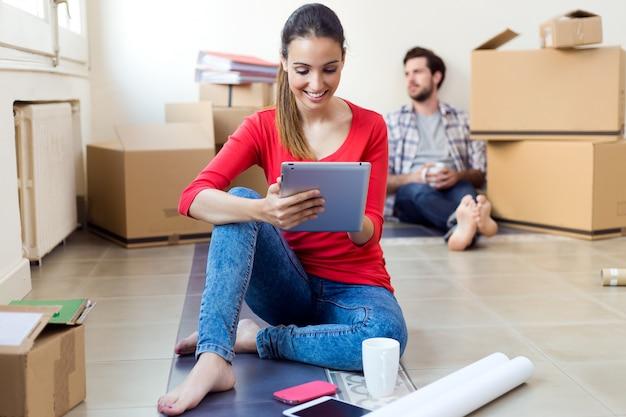 Jong koppel met digitale tablet rusten in hun nieuwe huis