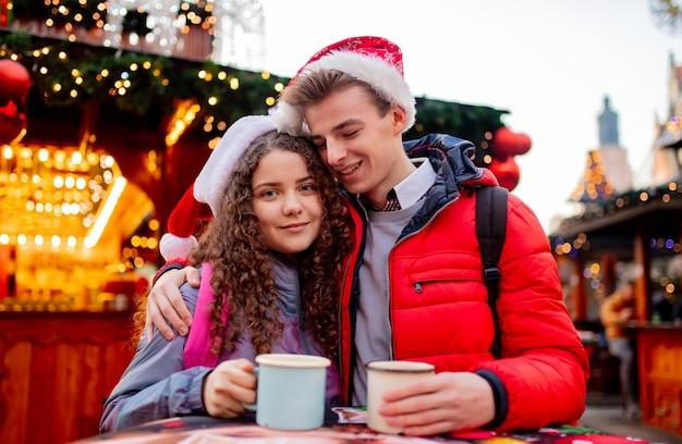 Jong koppel met drankjes op kerstmarkt in wroclaw, polen