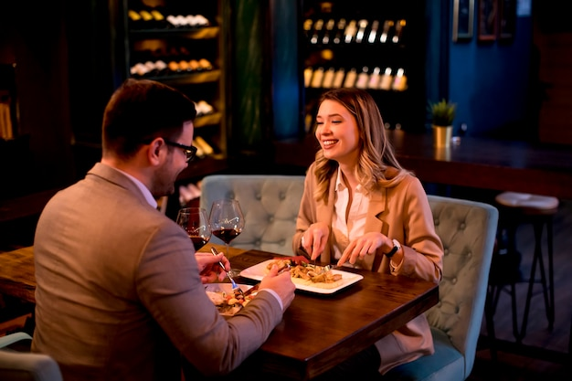 Jong koppel met een diner in het restaurant en het drinken van rode wijn