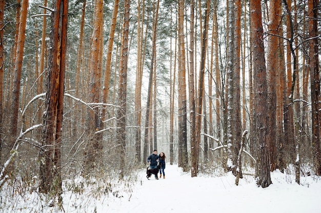 Jong koppel met een hond plezier in de winter