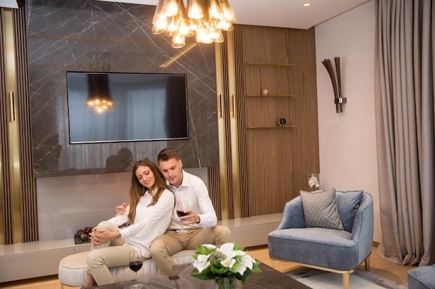 Jong koppel met een romantische avond met een glas rode wijn thuis in de moderne woonkamer