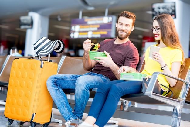 Jong koppel met een snack met lunchboxen in de wachtzaal van de luchthaven tijdens hun vakantie