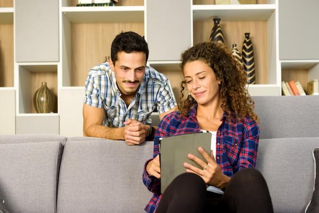 Jong koppel met een tablet-pc zitten samen kijken in hun woonkamer met een tevreden glimlach