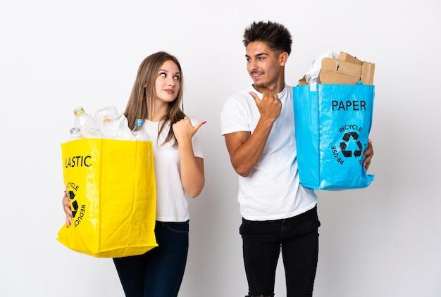 Jong koppel met een zak vol plastic en papier op wit wijzend naar de zijkant om een product te presenteren