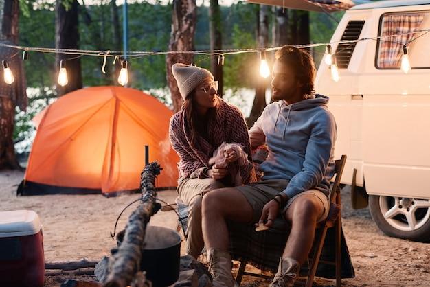 Jong koppel met elkaar praten tijdens hun camping in het bos met tent en busje op de achtergrond