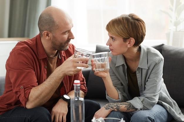 Jong koppel met glazen whisky praten met elkaar zittend op de bank in de huiskamer