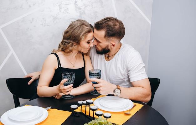 Jong koppel met glazen wijn met romantisch diner aan tafel