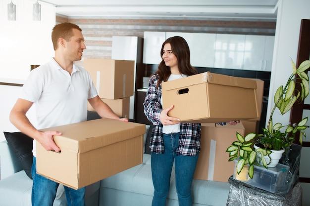 Jong koppel met grote kartonnen doos in nieuw huis. verhuizen.