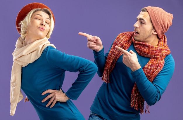 Jong koppel met hoed met sjaal op valentijnsdag verrast man wijst naar blij meisje geïsoleerd op blauwe achtergrond