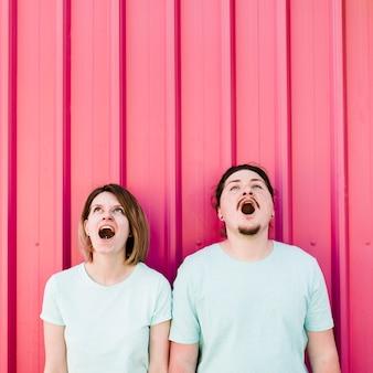Jong koppel met hun mond geopend op zoek tegen roze golfplaten