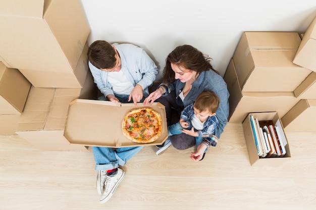 Jong koppel met hun zoon het eten van de pizza in hun nieuwe huis