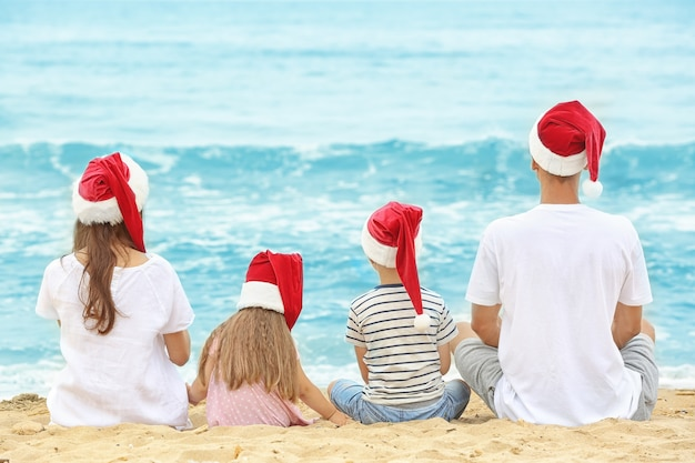 Jong koppel met kinderen op het strand. kerst concept