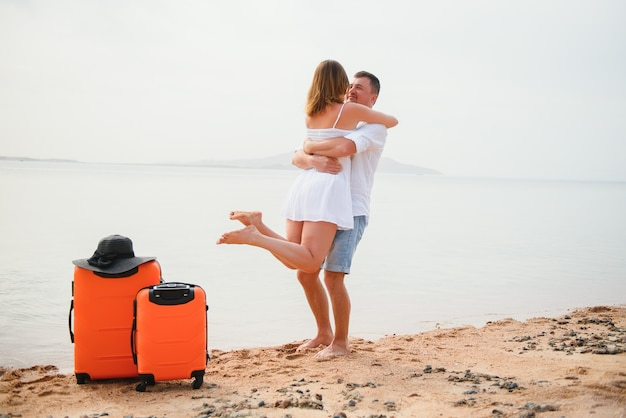 Jong koppel met koffer op het strand in zomerdag.