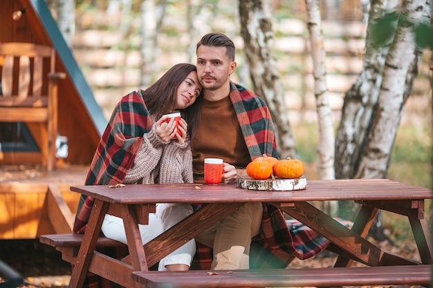 Jong koppel met koffie in hun achtertuin tijdens de herfst