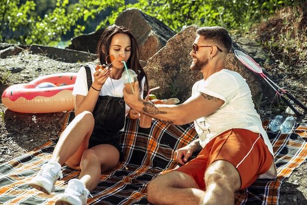 Jong koppel met picknick aan de rivier in zonnige dag. vrouw en man samen tijd doorbrengen op de natuur. plezier hebben, eten, spelen en lachen. concept van relatie, liefde, zomer, weekend.