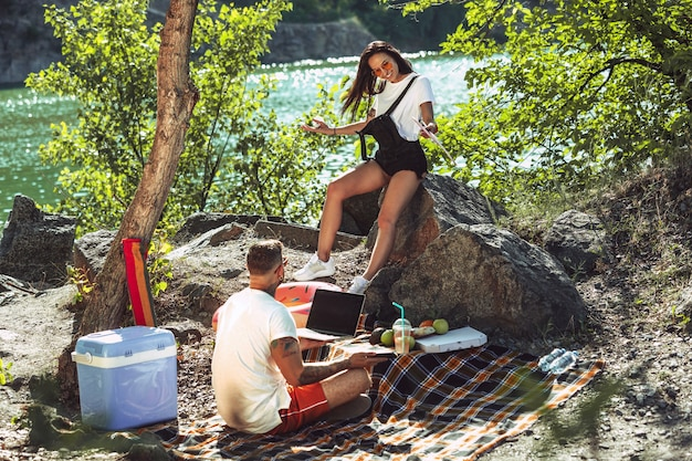 Jong koppel met picknick aan de rivier in zonnige dag.