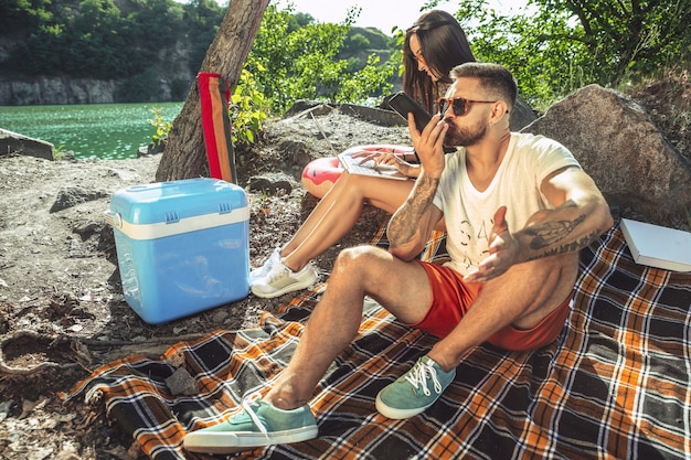Jong koppel met picknick aan de rivier in zonnige dag