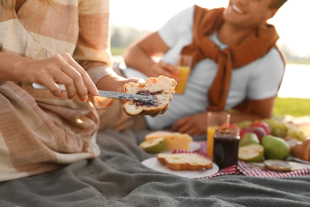 Jong koppel met picknick buiten op zonnige dag, close-up