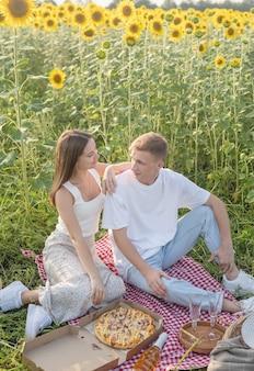 Jong koppel met picknick op zonnebloemveld