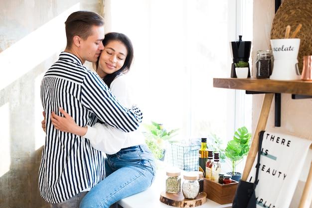 Jong koppel met romantisch moment in de keuken