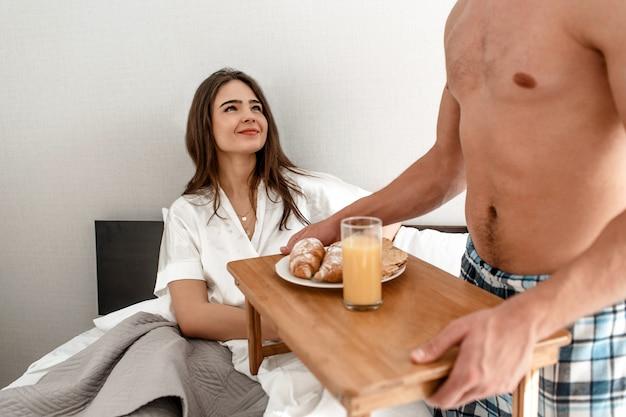 Jong koppel met romantisch ontbijt op bed. de gelukkige mooie vrouw kijkt gelukkig op haar liefje