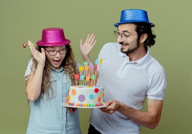 Jong koppel met roze en blauwe hoed glimlachende man geeft verjaardagstaart aan verrast meisje geïsoleerd op olijfgroen