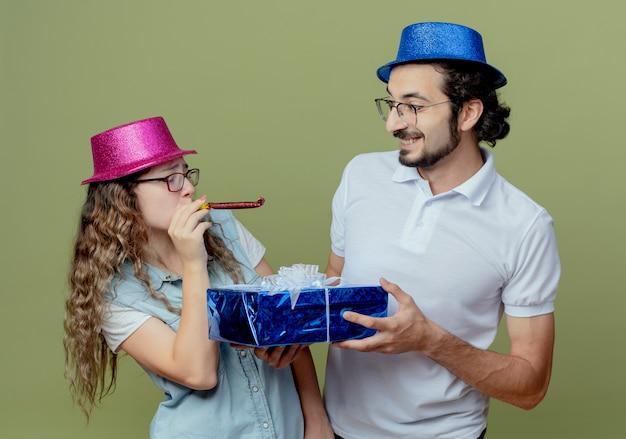 Jong koppel met roze en blauwe hoed kijken elkaar meisje blaast fluitje en jongen geeft geschenkdoos aan meisje geïsoleerd op olijfgroene muur