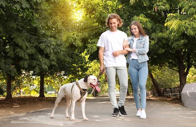 Jong koppel met schattige hond wandelen in het park