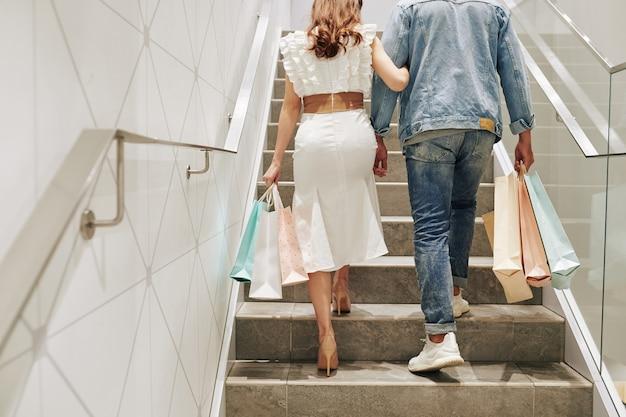 Jong koppel met veel boodschappentassen lopen de trap op na het doen van aankopen in de winkel
