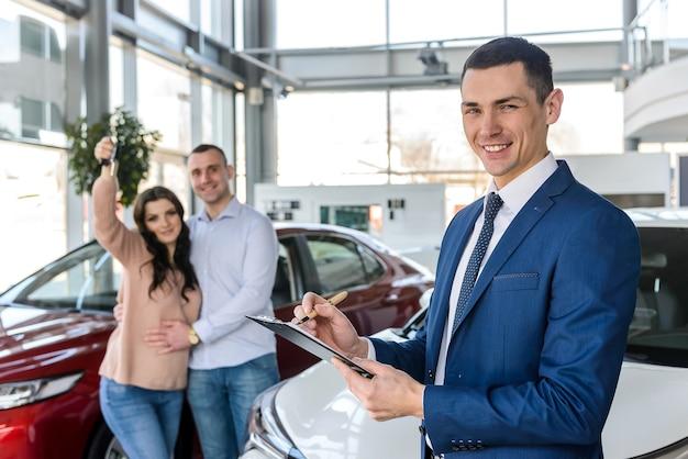 Jong koppel met verkoper in de buurt van nieuwe auto ondertekening contract