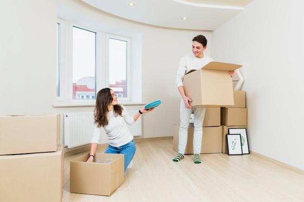 Jong koppel na het verplaatsen in een nieuw huis unboxing hun items