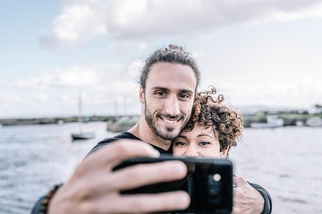 Jong koppel omarmd door de schouder maken een selfie met de haven en de zee onscherp