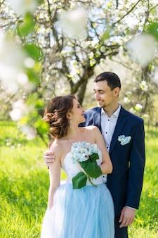 Jong koppel omarmen in bloeiende lentetuin. liefde en romantisch thema.