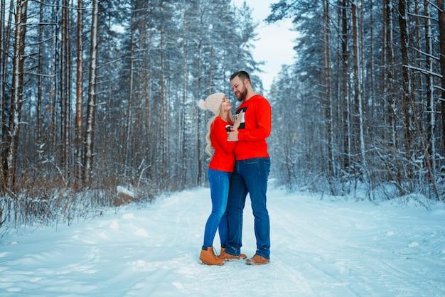 Jong koppel omarmen in winter forest. winter vakanties