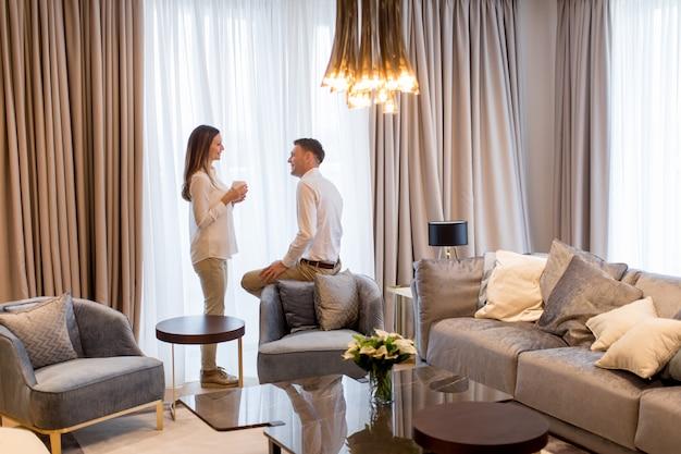 Jong koppel ontspannen en praten met koffiekopjes in de luxe kamer