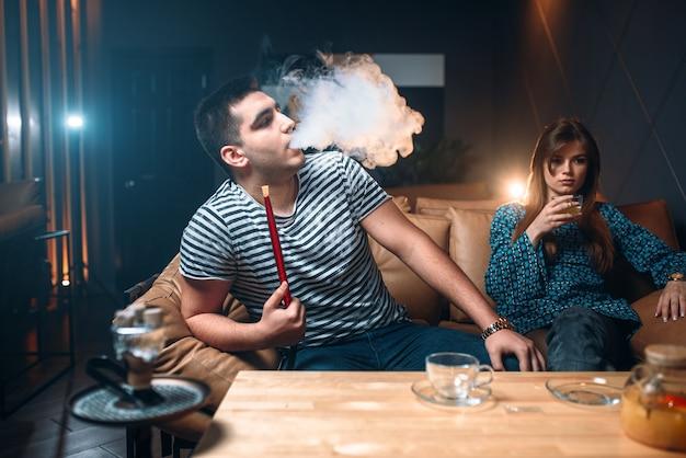 Jong koppel ontspannen en roken waterpijp