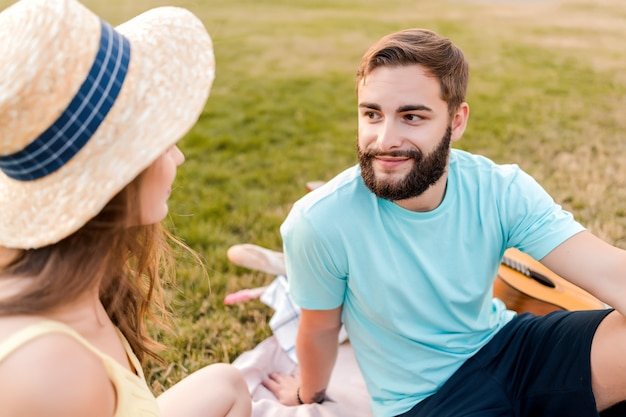 Jong koppel op de picknick in het park praten en ontspannen