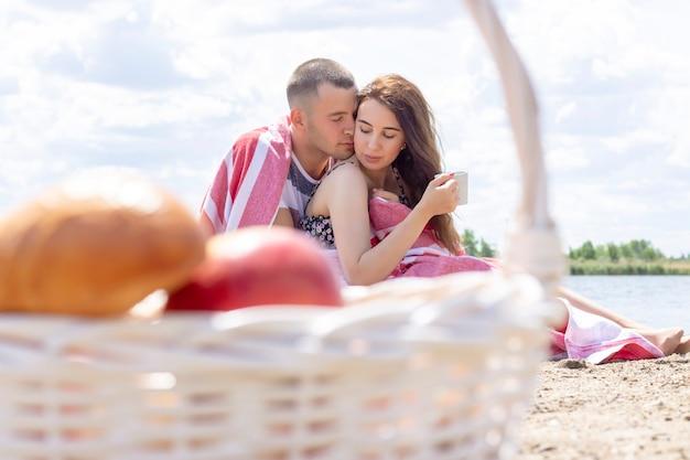 Jong koppel op een zomerpicknick aan zee