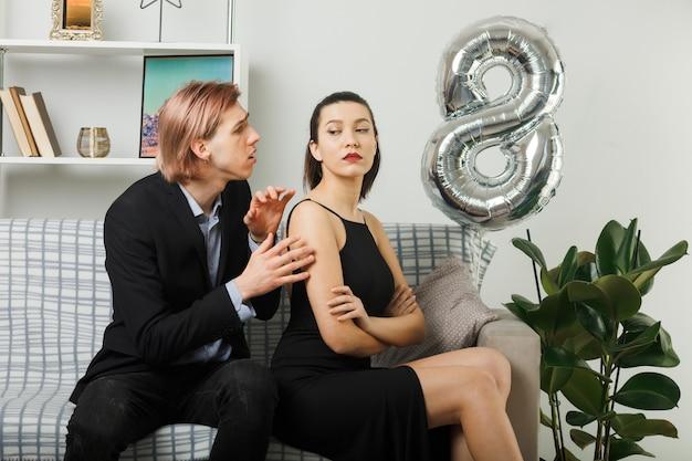 Jong koppel op gelukkige vrouwendag, trieste man die naar een streng meisje kijkt dat op de bank in de woonkamer zit