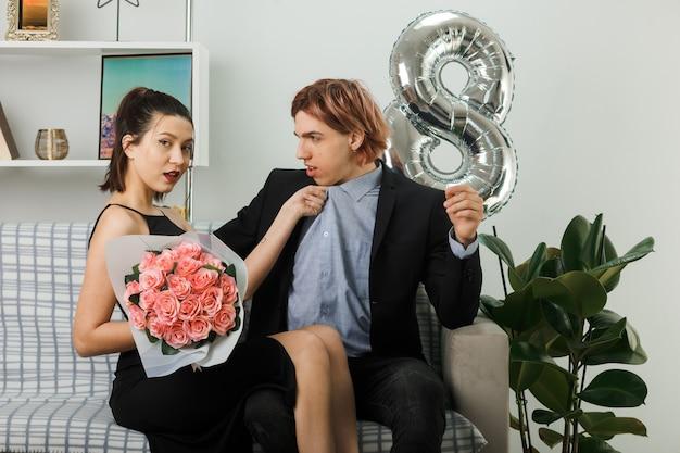 Jong koppel op gelukkige vrouwendag vrouw met boeket en greep zijn kraag zittend op de bank in de woonkamer