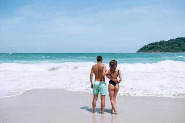 Jong koppel op het strand in zwempakken knuffelen en kijken naar de zee